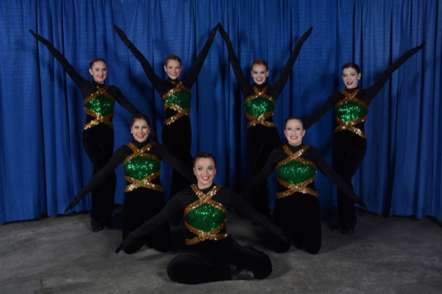 dancers in black outfits with green and gold sequins